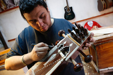 Musical instrument maker Abraham Becerra, restores an Indian traditional musical instrument called sarangi at his workshop at Vina del Mar
