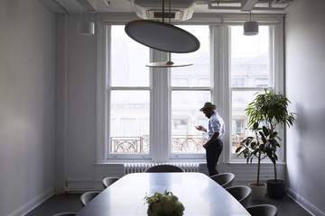 Businessman using mobile phone while standing by window in conference room