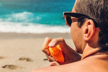 Sun cream protection. Man sprays sun cream on his shoulder. Skin care concept. Healthy skin on vacation.