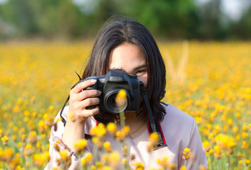 Asian woman photographer take photo camera in yellow flower field