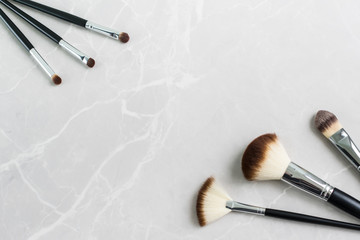Set of six  black makeup brushes on a marble surface with copy space.