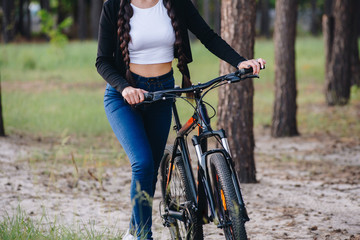 Bicyclist at the summer sunset on the desert road in the reserve territory. Full length image of female bicycle. Extreme mountain bike sport athlete woman riding outdoors lifestyle trail