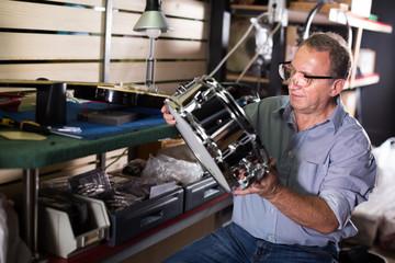 Musician is repairing instruments indoors
