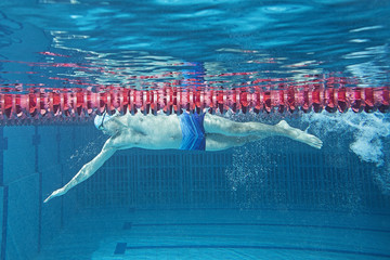 Man in swimming pool. Underwater