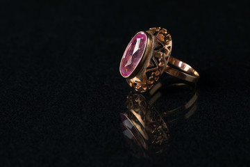 Golden ring with a ruby on a black background