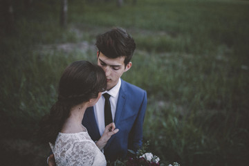 High angle view of bride with groom standing on grassy field in forest