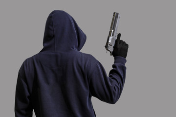 HoodedHooded man with a gun in hand isolated on grey background man with a gun in hand isolated on white background