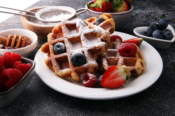 Traditional belgian waffles with fresh fruit and powder sugar on wooden board