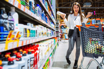 woman can't decide what shampoo to buy. shopping concept.