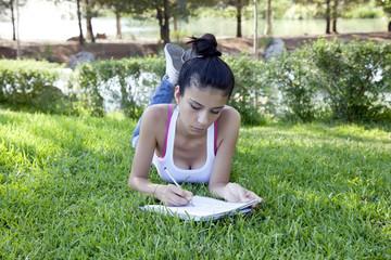 Beatiful Teenage Girl Studying in the Park.