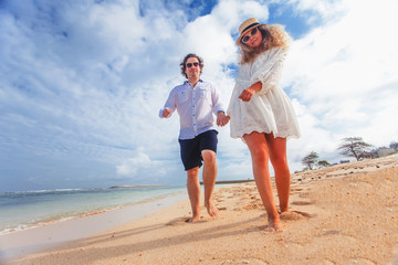 Wedding couple just married holds hands and walking at beach
