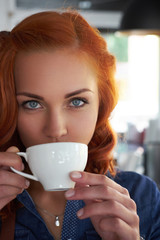 A beauty redhead female barista drinks a coffee, at the coffee shop.