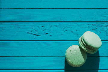 Two green macaron or macaroons on a turquoise wooden background, almond cookies in pastel tones, top view, copy space