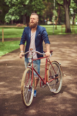 Male dressed in casual clothes, walking with a retro bicycle in a city park.