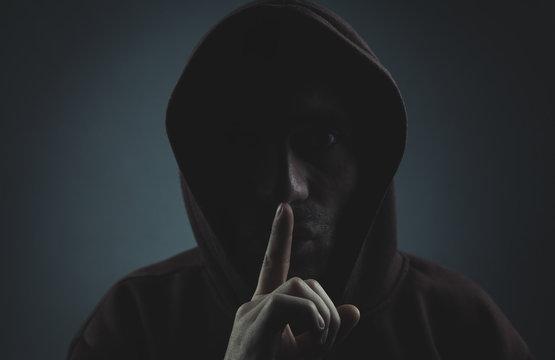 Thief making silence gesture.
