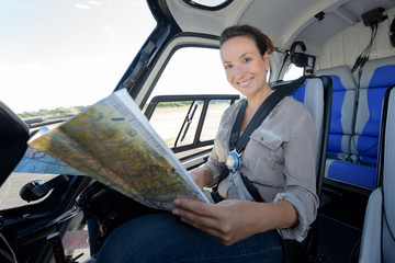 young woman helicopter pilot checking a map