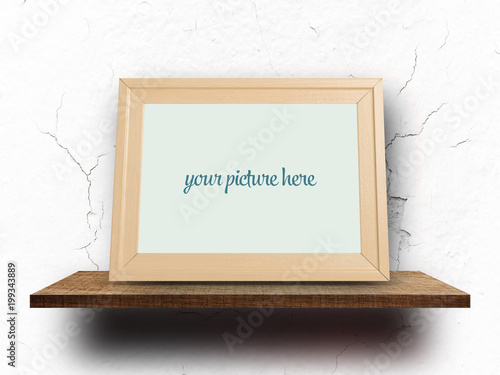 Empty wooden frame mock up on shelf with cracked white wall\