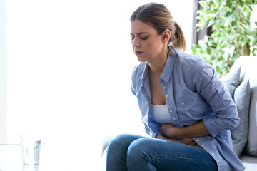 Unhealthy young woman with stomachache leaning on the couch at home.