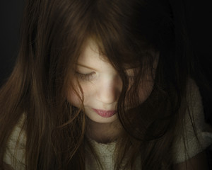 Close-up of cute girl with brown hair in darkroom