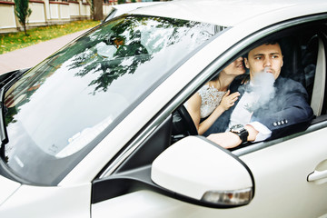 newlywed couple, groom and bride, in car