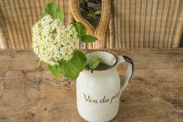 """Spring fllowers in old jug with text in french """"wine of country"""""""