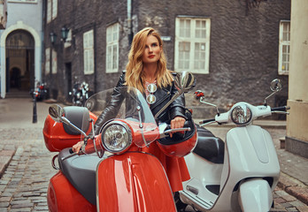 Sexy blonde girl wearing stylish clothes standing on an old street with two retro scooters.