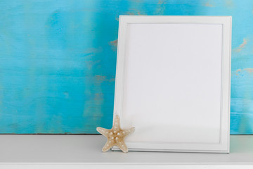 Mock-up with white frame and star fish with a turquoise rustic background