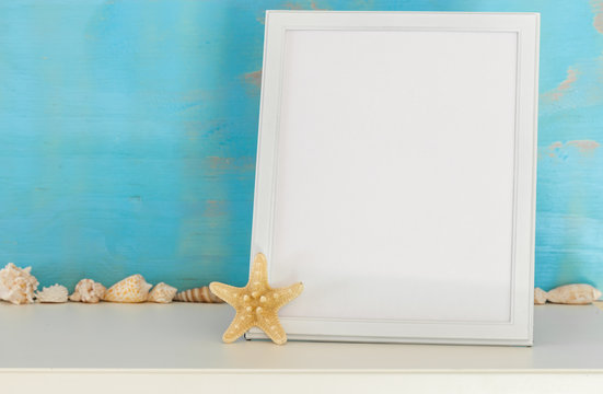 Mock-up with white frame and star fish and sea shells on a turquoise rustic background