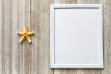 Mock-up with white frame and star fish on a rustic wooden background with copy space