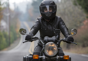 Portrait of female biker riding motorcycle on country road