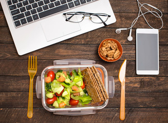 Fotobehang Assortiment Healthy business lunch at workplace. Salad, salmon, avocado and nuts lunch box on working desk with laptop, smartphone, glasses and headphones.
