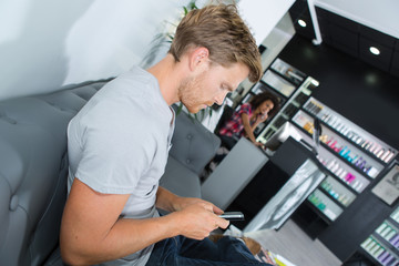 male customer with phone waiting at hair salon