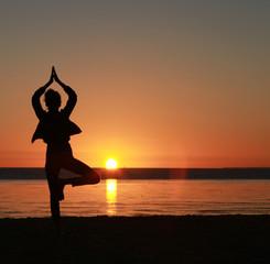 Posture zen au coucher de soleil en bord de mer
