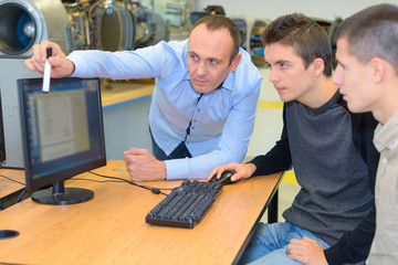 Tutor advising two male students using computer