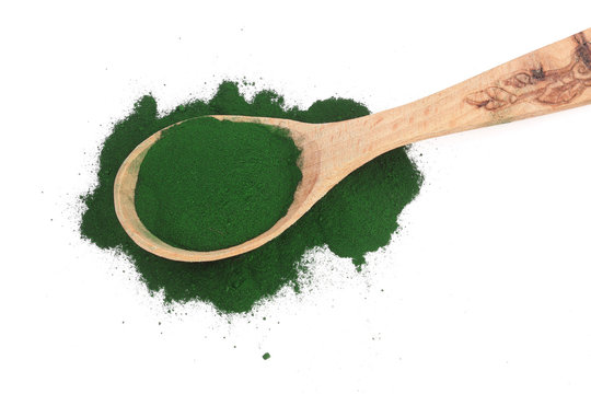 Spirulina algae powder in wooden spoon isolated on white background. Top view