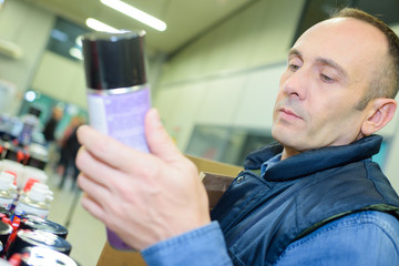 cheerful man choosing insects killer spray in household section