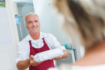 Butcher handing meat to customer
