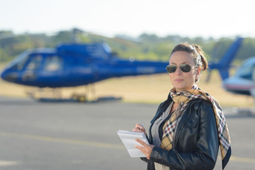 pretty pilot woman on helicopter background
