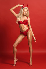 Sexy blonde woman in red lingerie over red background