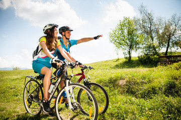 ACTIVE Young couple biking on a forest road in mountain on a spring day Wall mural