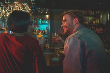 Side view cheerful female talking with happy man. Glad couple drinking alcohol beverage in bar concept