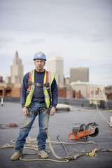 Portrait of male worker standing on building at construction site against cloudy sky