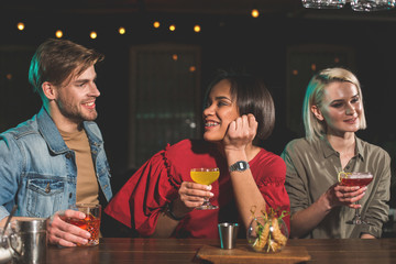 Outgoing bearded male telling with smiling pretty girl. She sitting near glad lady. Beaming comrades drinking beverage in club concept