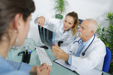 doctor in office examining x-ray and discussing with patient