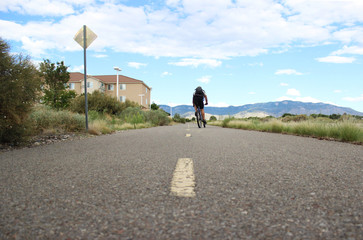 Solo man bicycling down empty road towards the mountains in New Mexico