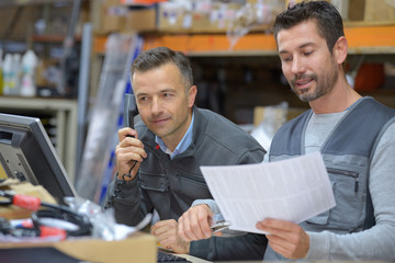 manager talking on the phone next to worker in warehouse