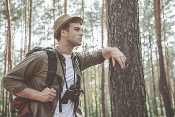 Profile of serious young hiker is standing with backpack and binoculars in forest while leaning on tree. He is looking aside thoughtfully