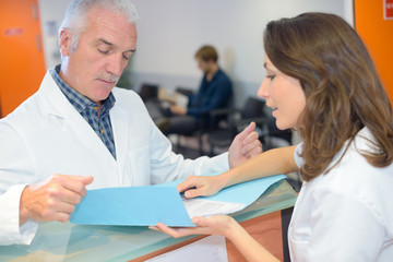 Doctor talking to secretary at reception