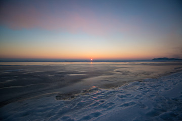 Frozen sea on sunset. Beautiful natural seascape on winter time. Endless ice to horizon. Ice surface for product placing.