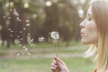 tranquil woman standing in park and blowing on dandelion. Copy space in left side